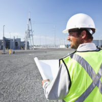 engineer at power station holding plans
